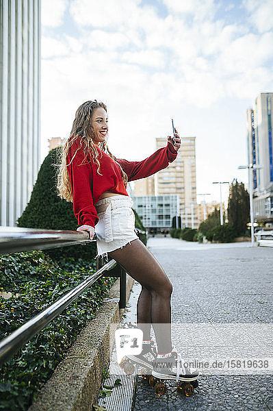Lächelnde junge Frau auf Rollschuhen beim Selfie in der Stadt