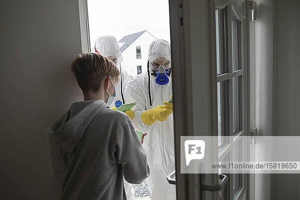 Wissenschaftler  die Schutzkleidung tragen und die Leute an der Tür informieren