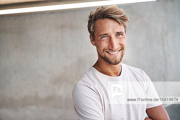 Porträt eines lächelnden jungen Mannes mit weißem T-Shirt