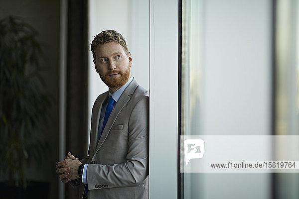 Porträt eines aus dem Fenster blickenden Geschäftsmannes