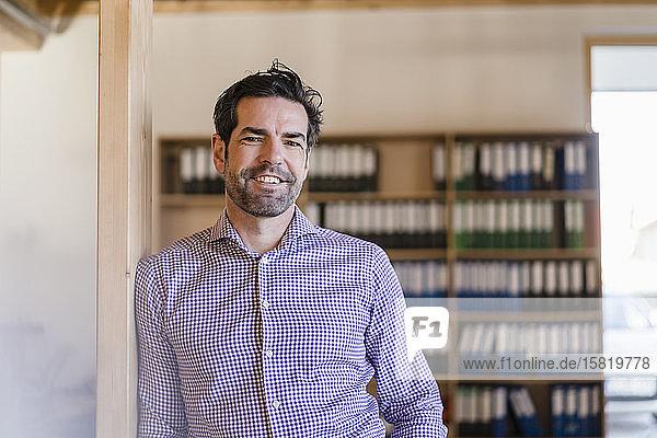 Porträt eines lächelnden  an Balken gelehnten Geschäftsmannes in einem hölzernen Großraumbüro