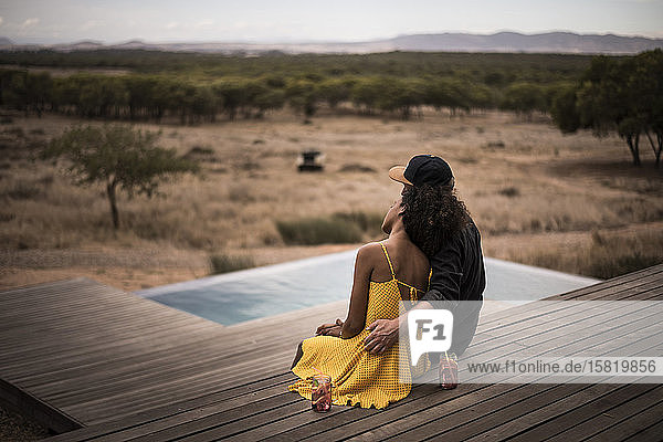 Rückansicht eines Paares  das auf dem Deck einer Lodge sitzt  Kapstadt  Südafrika