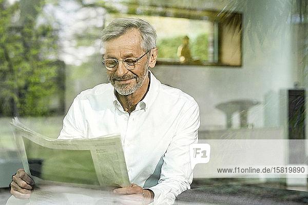 Älterer Mann mit grauen Haaren im modern gestalteten Wohnzimmer beim Zeitungslesen