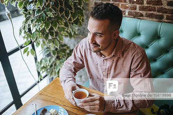 Mann in einem Cafe mit einer Tasse Tee  der aus dem Fenster schaut