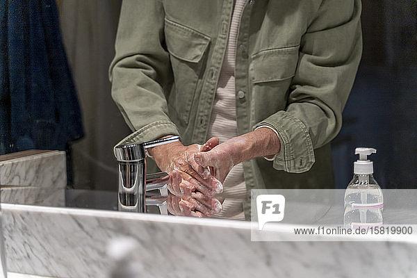 Spiegelbild eines Mannes  der sich die Hände mit Desinfektionsmittel wäscht
