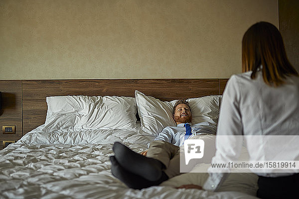 Businessman lying on bed in hotel room looking at businesswoman