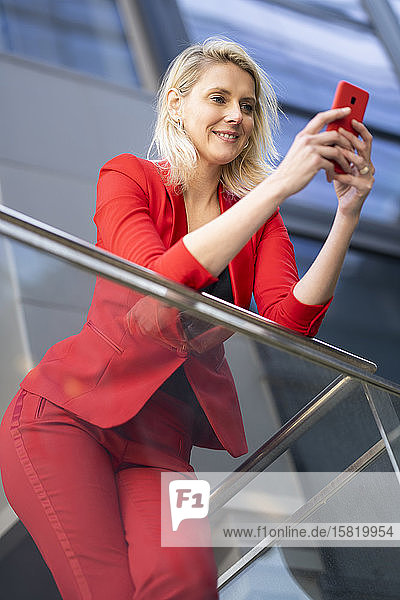 Blond businesswoman wearing red suit and checking smartphone