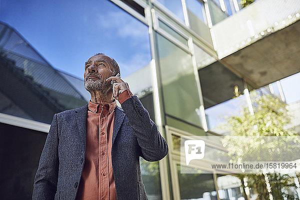 Leitender Geschäftsmann in der Stadt  telefoniert