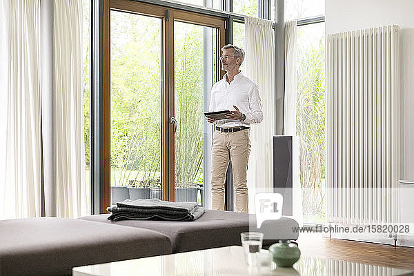 Senior man with grey hair in modern design living room standing at window holding tablet