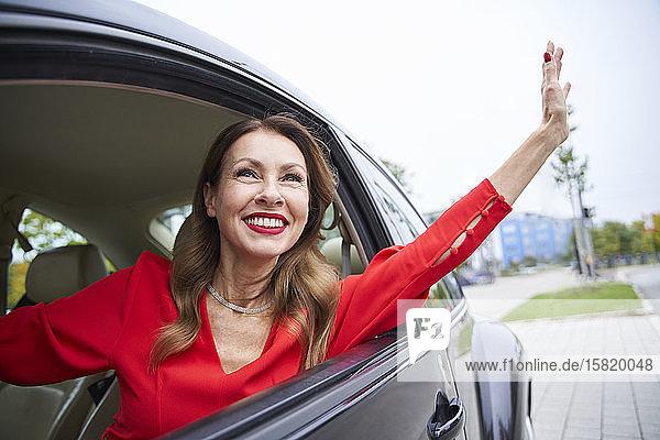 Porträt einer glücklichen  reifen Frau  die aus dem Autofenster schaut und winkt