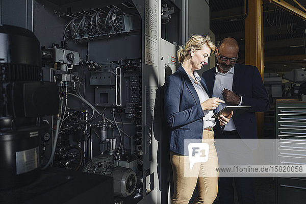Geschäftsmann und Geschäftsfrau mit Tabletten in einer Fabrik