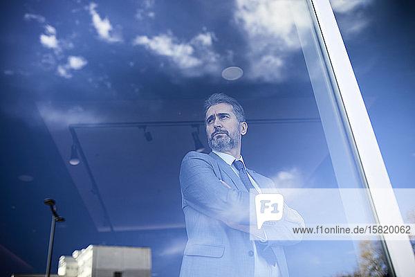 Portrait of a mature businessman behind windowpane