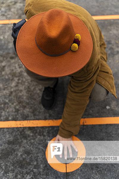 Draufsicht eines Mannes mit Hut  der seine Hand auf einen Kreis auf dem Boden legt