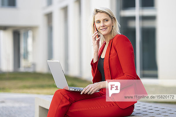 Blond businesswoman wearing red suit and using laptop and smartphone  sitting on a bench