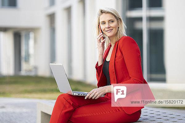 Blonde Geschäftsfrau im roten Anzug  mit Laptop und Smartphone  auf einer Bank sitzend