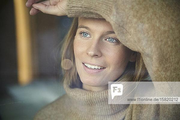 Porträt einer lächelnden blonden jungen Frau hinter einer Fensterscheibe