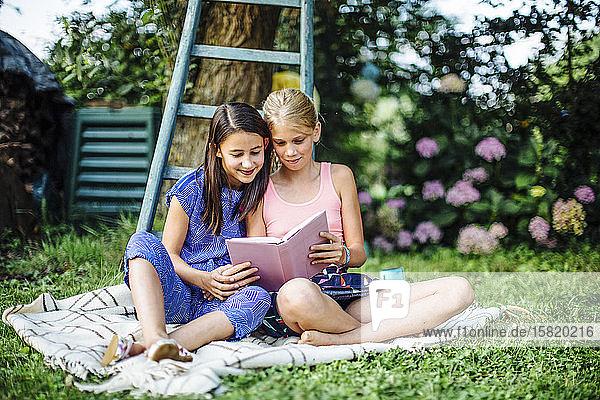 Lächelnde Mädchen lesen gemeinsam ein Buch im Garten Lächelnde Mädchen lesen gemeinsam ein Buch im Garten