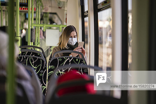 Woman with face mask sitting in tram  using smartphone