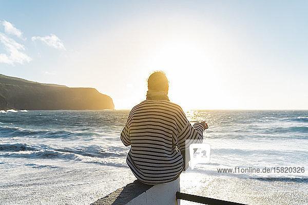 Mann meditiert bei Sonnenuntergang an der Küste  Sao-Miguel-Insel  Azoren  Portugal