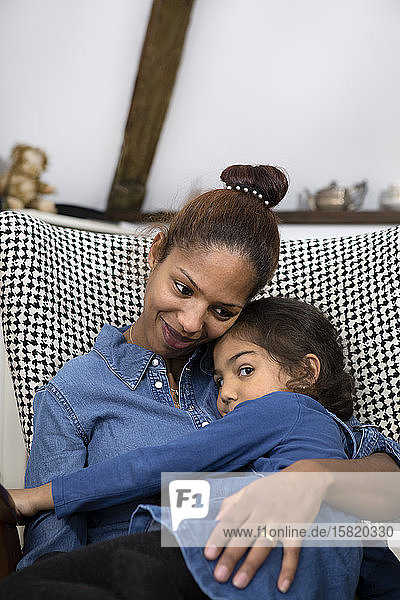 Portrait of happy mother cuddling with little daughter on an armchair
