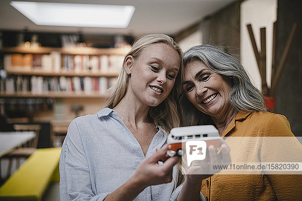 Porträt einer glücklichen Mutter und einer erwachsenen Tochter mit einem Lieferwagenmodell