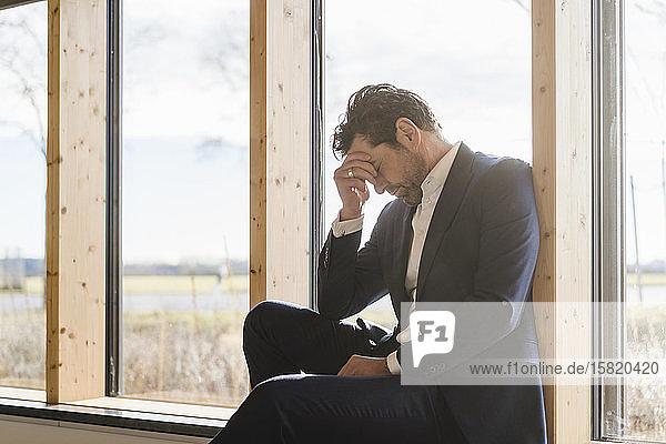 Müde Geschäftsmann sitzt im Büro am Fenster