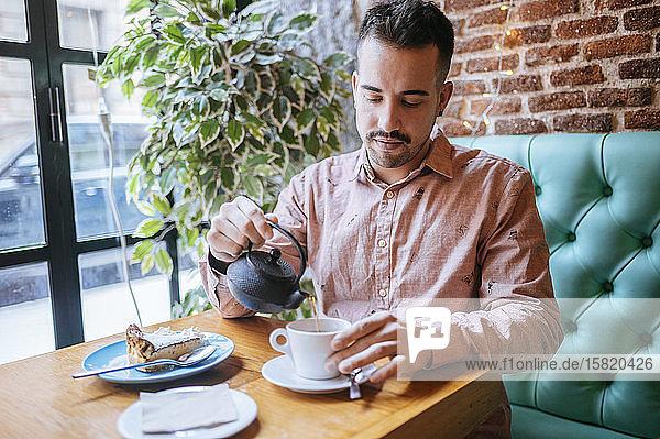 Mann in einem Café  der Tee in eine Tasse gießt