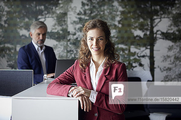 Porrait of smiling businesswoman in office with businessman in background