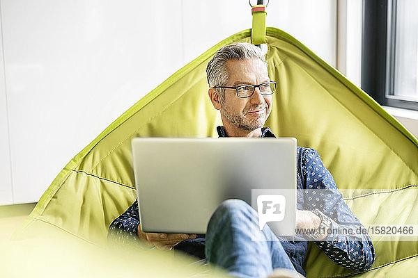 Lächelnder Geschäftsmann in der Hängematte sitzend  mit Laptop