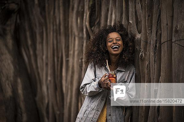 Porträt einer lachenden Frau  die frischen Eistee trinkt