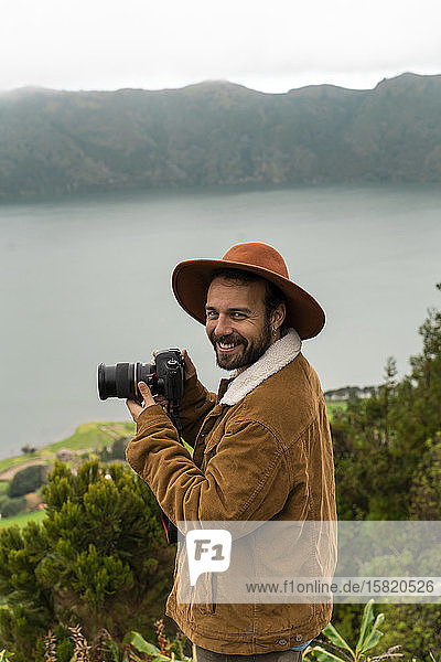Porträt eines lächelnden Mannes mit Kamera an einem See stehend  Sao-Miguel-Insel  Azoren  Portugal