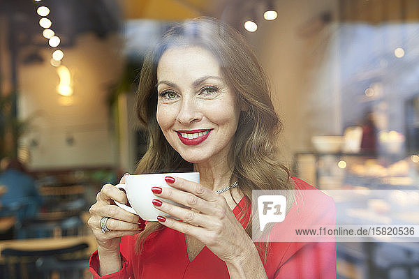 Portrait of smiling mature woman with cup of coffee behind windowpane