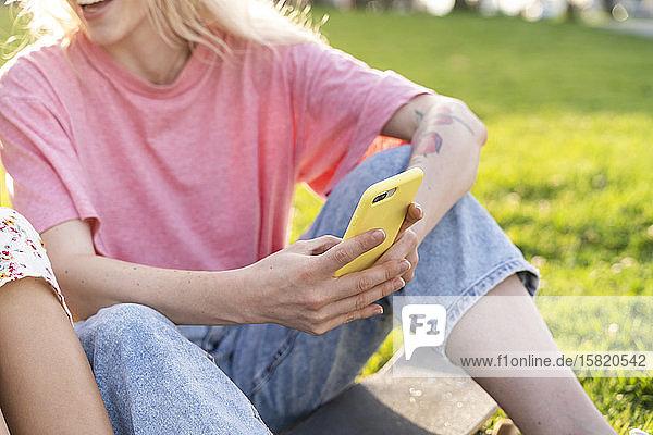 Nahaufnahme einer jungen Frau mit einem Smartphone in der Hand auf einer Wiese