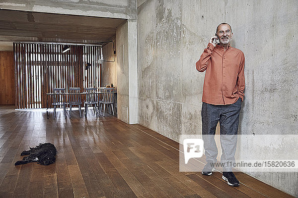 Kreativer Geschäftsmann telefoniert in seinem minimalistischen Büro  Hund liegt auf dem Boden