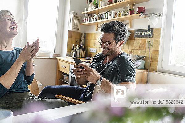 Glückliches Paar sitzt am Tisch in der Küche und benutzt ein Smartphone
