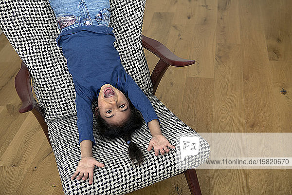 Portrait of little girl hanging upside down from backrest of an armchair having fun