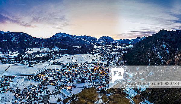 Deutschland,  Bayern,  Reit im Winkl,  Helikopteransicht eines schneebedeckten Bergdorfes in der Morgendämmerung