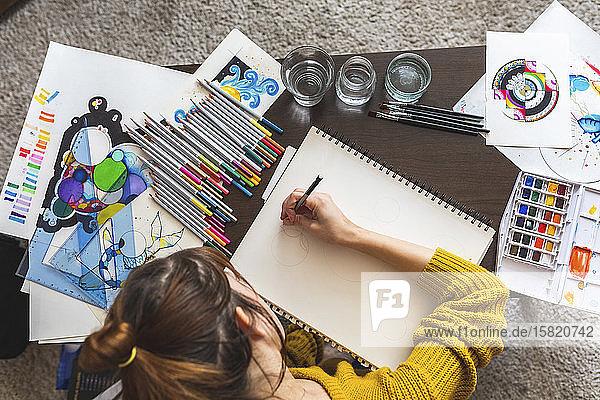 Scherenschnittansicht einer Frau  die zu Hause zeichnet