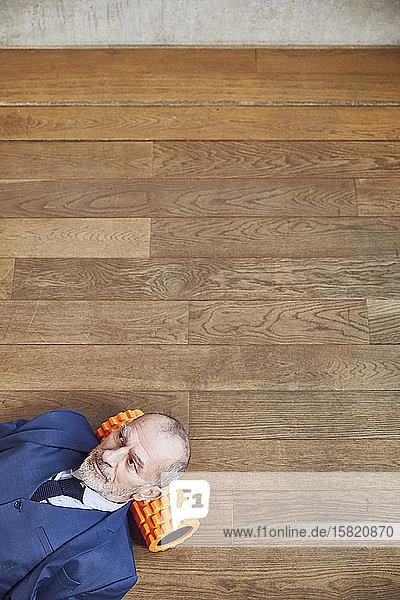 Älterer Geschäftsmann entspannt sich auf Holzboden  ruht auf Faszienrolle