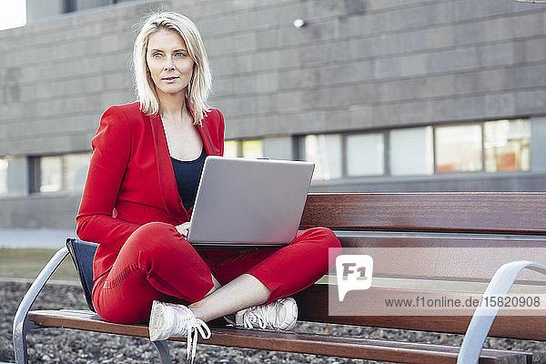 Blonde Geschäftsfrau in rotem Anzug und mit Laptop auf einer Bank