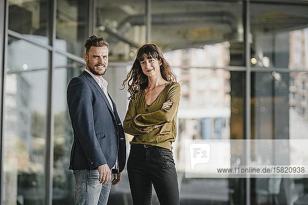 Porträt eines lächelnden Geschäftsmannes und einer lässigen Geschäftsfrau im Freien