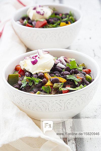 Zwei Schüsseln schwarze Bohnensuppe mit Paprika  Koriander  Sauerrahm und roten Zwiebeln