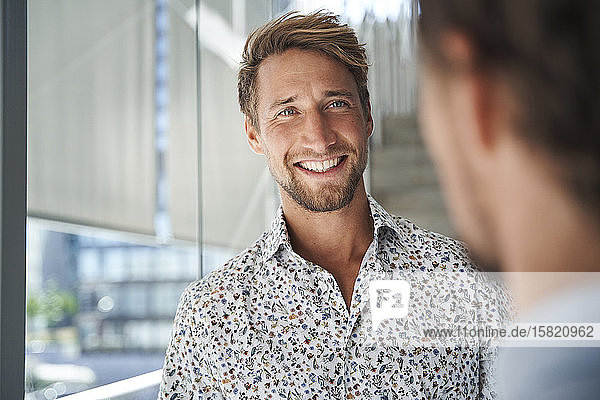 Portrait of happy young businessman looking at colleague