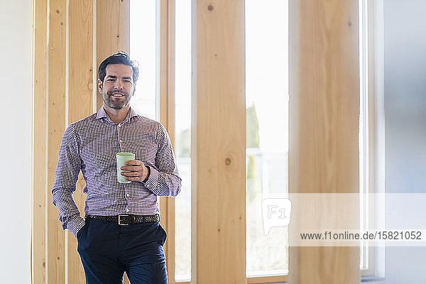 Porträt eines lächelnden Geschäftsmannes  der eine Tasse in einem hölzernen Großraumbüro hält