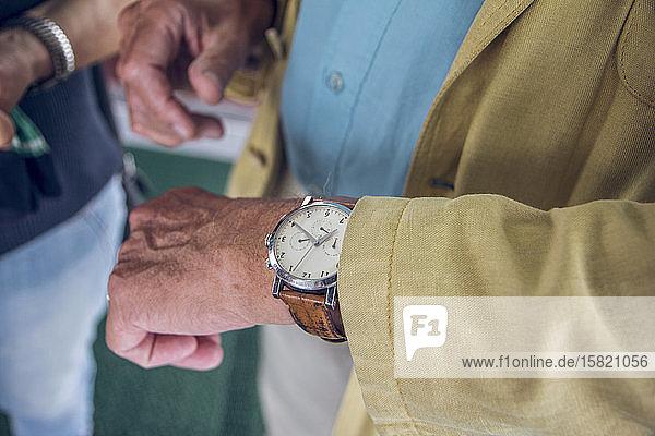 Nahaufnahme der Armbanduhr  älterer Mann prüft die Zeit