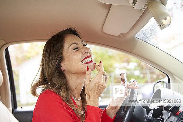 Reife Frau mit roten Lippen und Nägeln im Auto