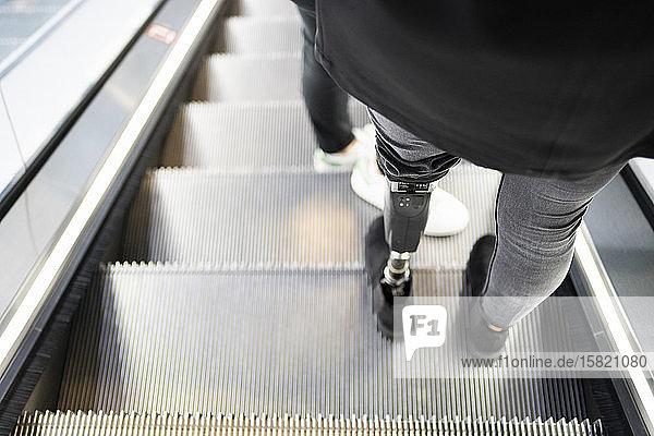 Nahaufnahme einer auf der Rolltreppe stehenden Frau mit Beinprothese