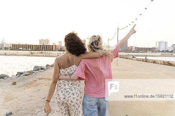 Rückansicht von zwei jungen Frauen auf der Uferpromenade bei Sonnenuntergang