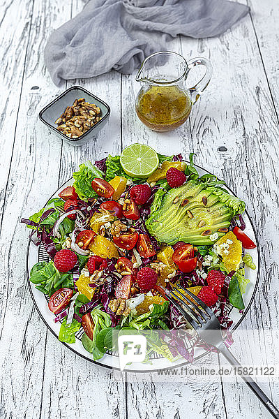 Plate of colorful mixed salad with feta cheese  common beet  walnuts  pine nuts  raspberries  oranges and corn salad