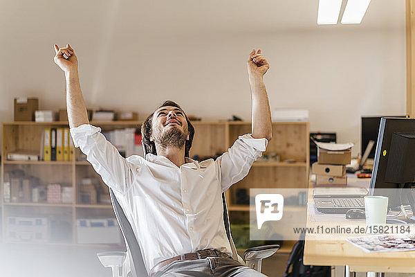Geschäftsmann jubelt am Schreibtisch im Büro